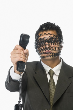 obscured: Businessman showing telephone receiver with his obscured face