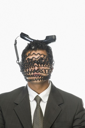 obscured face: Businessmans face wrapped with telephone cord with its receiver on his head