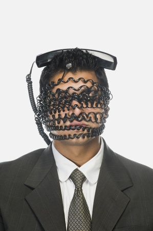 Businessman's face wrapped with telephone cord with it's receiver on his head Stock Photo - 10166617