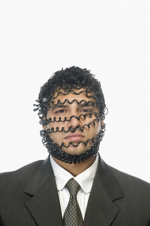 Portrait of a businessman wrapped with telephone cord Stock Photo - 10169307