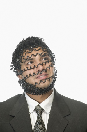 Close-up of a businessman's face covered with phone cord Stock Photo - 10166448