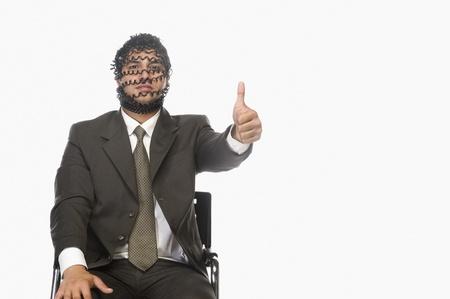 Retrato de un hombre de negocios mostrando pulgares con su rostro cubierto con cable telefónico Foto de archivo - 10124221