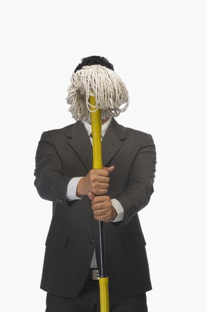 indian subcontinent ethnicity: Businessman holding a broom in front of his face