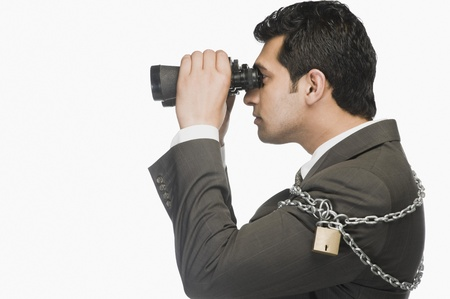 Businessman locked in chains and looking through binoculars Stock Photo - 10124420
