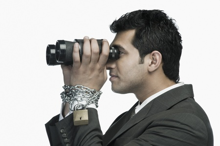 Businessman locked in chains and looking through binoculars Stock Photo - 10169378