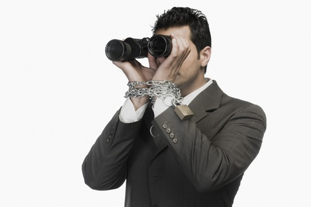 Businessman locked in chains and looking through binoculars Stock Photo - 10125331