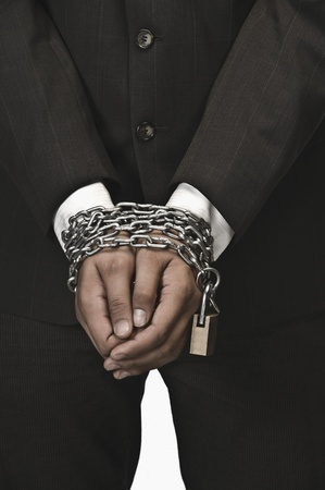 Close-up of a businessman's hands locked with chains Stock Photo - 10169059