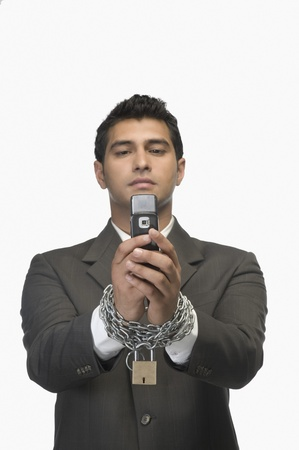 Businessman looking at a mobile phone with his hands in chains Stock Photo - 10124127