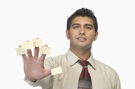 Portrait d'un homme d'affaires avec des notes adhésives sur ses doigts