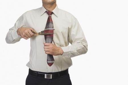 demotion: Businessman cutting his tie by scissors
