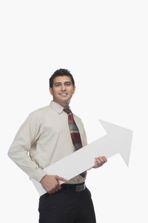 business sign: Portrait of a businessman smiling and holding an arrow sign LANG_EVOIMAGES