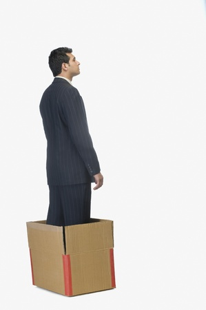 Businessman standing in a cardboard box Stock Photo - 10124284