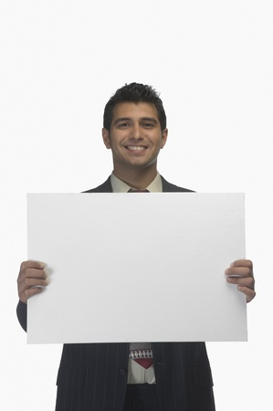 Portrait of a businessman holding a blank placard and smiling Imagens