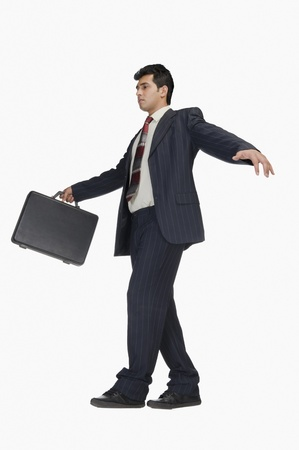 carefully: Businessman holding a briefcase and walking carefully