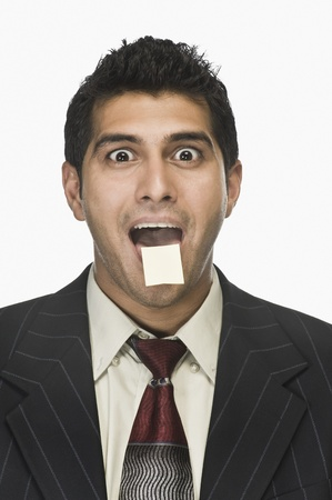 Portrait of a businessman surprised with an adhesive note on his lips Stock Photo - 10166549