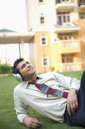 Businessman lying on the grass and listening to music Stock Photo - 10124698