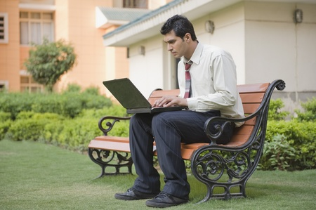 Businessman sitting on the bench and using a laptop Stock Photo - 10166408