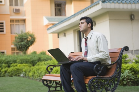 Businessman sitting on the bench and using a laptop Stock Photo - 10124771