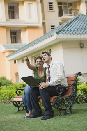 indian subcontinent ethnicity: Couple sitting on the bench with laptop and pointing