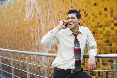 Businessman leaning against a railing and talking on a mobile phone Stock Photo - 10169293