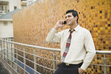 Businessman leaning against a railing and talking on a mobile phone Stock Photo - 10166456