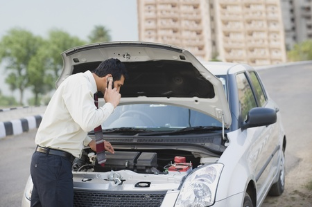 Businessman on the phone looking under the car hood Stock Photo - 10125065