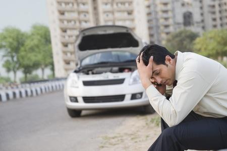 Bezorgd zakenman praten op een mobiele telefoon na de mislukking van zijn voertuig