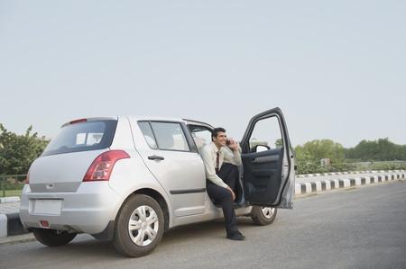 사업가 차에 앉아 휴대 전화에 얘기 스톡 콘텐츠
