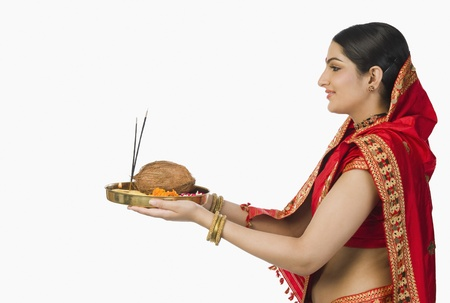 indian subcontinent ethnicity: Woman in red mekhla holding religious offering