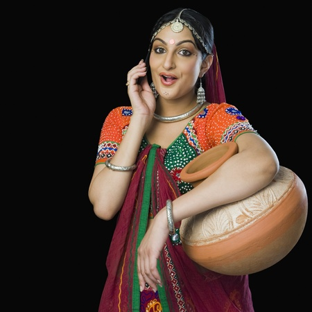 Beautiful woman in colorful lehenga choli carrying water pot Stock Photo - 10124662