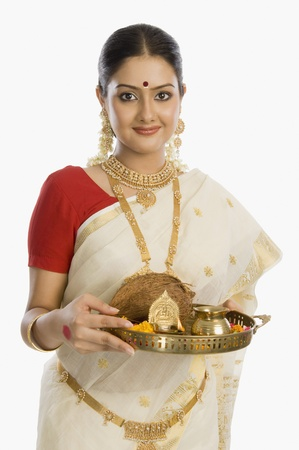 one adult only: Portrait of a South Indian woman holding a plate of religious offerings LANG_EVOIMAGES