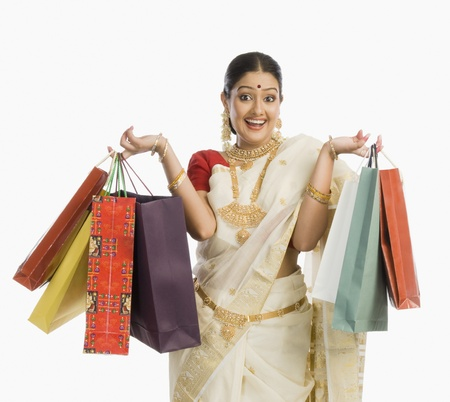 indian subcontinent ethnicity: South Indian woman holding shopping bags and smiling