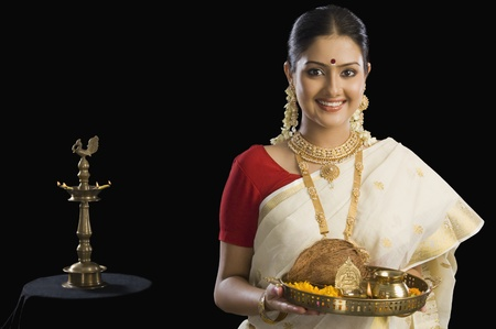 indian subcontinent ethnicity: Portrait of a South Indian woman holding a plate of religious offerings LANG_EVOIMAGES