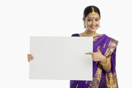 indian subcontinent ethnicity: Beautiful woman in traditional Assamese dress holding a blank placard and smiling