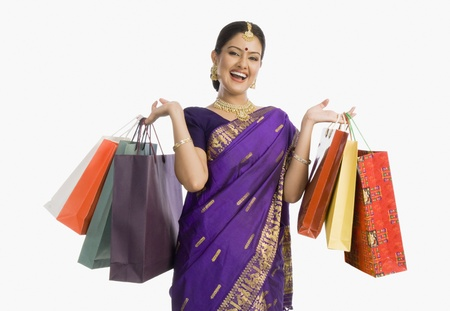 indian subcontinent ethnicity: Beautiful Assamese woman holding shopping bags and smiling