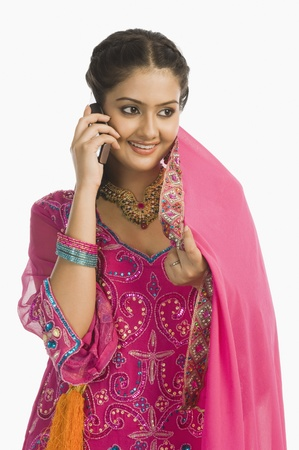 salwar: Woman wearing a salwar kameez and talking on a mobile phone LANG_EVOIMAGES