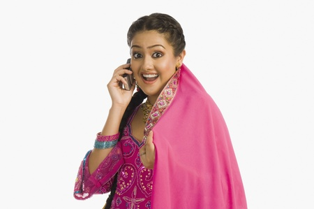 Woman wearing a salwar kameez and talking on a mobile phone LANG_EVOIMAGES