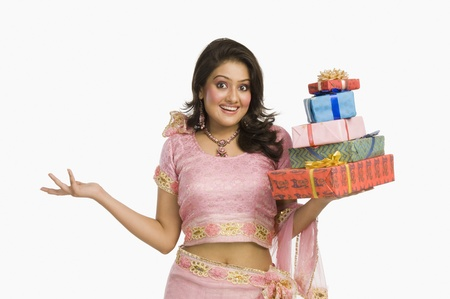Portrait of a beautiful woman in traditional dress holding gifts and smiling Stock Photo - 10124431