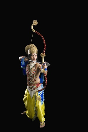 Stage artist dressed-up as Rama and holding a bow and arrow Stock Photo - 10124006