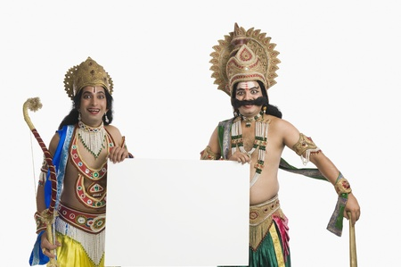 Two men dressed-up as Rama and Ravana and holding a blank placard Imagens