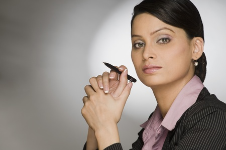 thinking woman: Close-up of a businesswoman holding a pen
