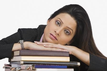 Portret van een zakenvrouw rust haar gezicht op boeken