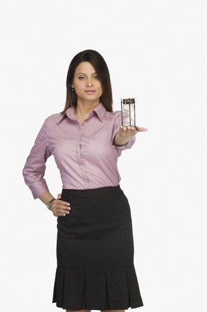 Businesswoman holding an hourglass