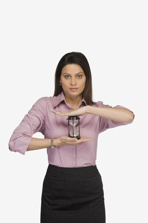 Businesswoman holding an hourglass Stock Photo - 10166320