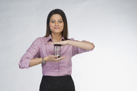 Businesswoman holding an hourglass Stock Photo - 10125122