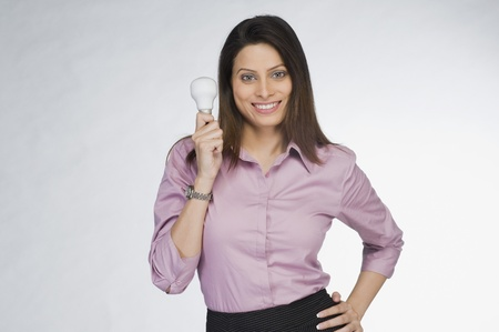 Businesswoman holding a light bulb and smiling Stock Photo