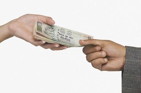 Vrouw geven van geld aan een man Stockfoto