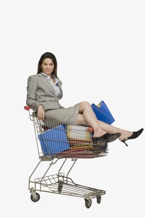 Businesswoman sitting in a shopping cart with files Stock Photo - 10125203