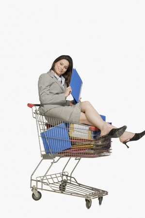 woman shopping cart: Businesswoman sitting in a shopping cart with files LANG_EVOIMAGES