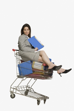 Businesswoman sitting in a shopping cart with files Stock Photo - 10125216